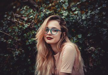 eine Frau mit roten Lippen, die nahe den grünen Pflanzen steht