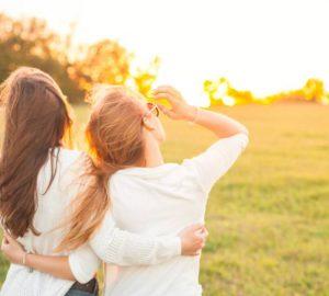 Rückansicht von Freundinnen auf Rasenfläche während des Sonnenuntergangs