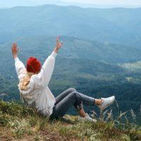 oben auf dem Berg sitzt und genießt eine Blondine mit einer roten Mütze