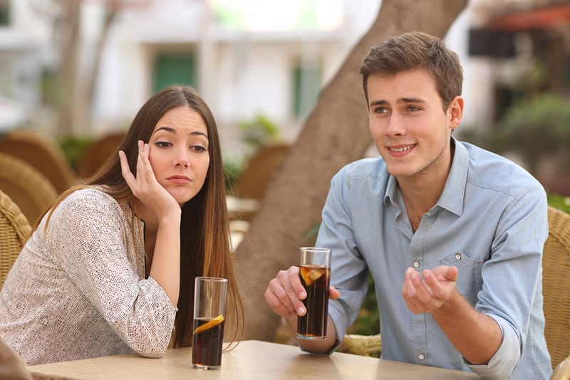 Eine gelangweilte Frau sitzt neben einem Mann und spricht mit ihr über ein Date