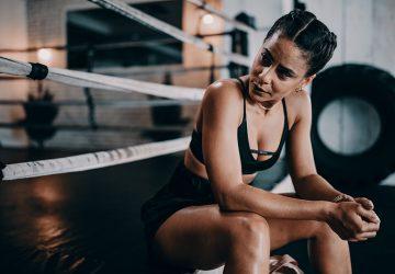 eine Frau, die beiseite schaut und in der Nähe des Boxrings sitzt