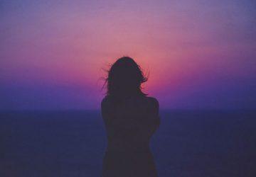 Das Mädchen beobachtet den Sonnenuntergang