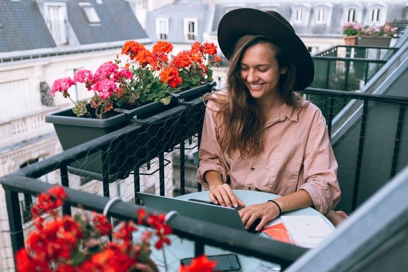 Auf dem Balkon voller roter Ratsmitglieder am Tisch sitzt eine lächelnde Frau mit einem schwarzen Hut auf dem Kopf und benutzt einen Laptop