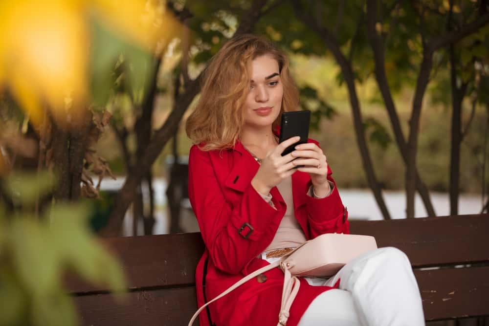 Auf einer Holzbank im Park sitzt ein Pavuša in einem roten Mantel und schreibt eine SMS