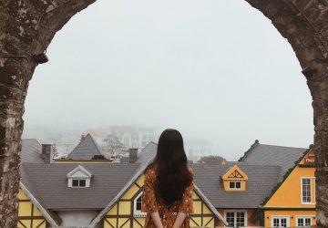 Eine Frau in einem bunten Kleid steht auf einer Steinmauer und beobachtet die Stadt