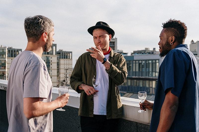 Baumfreunde unterhalten sich auf dem Dach und trinken Wein