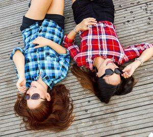 zwei Freundinnen, die auf dem Holzboden liegen