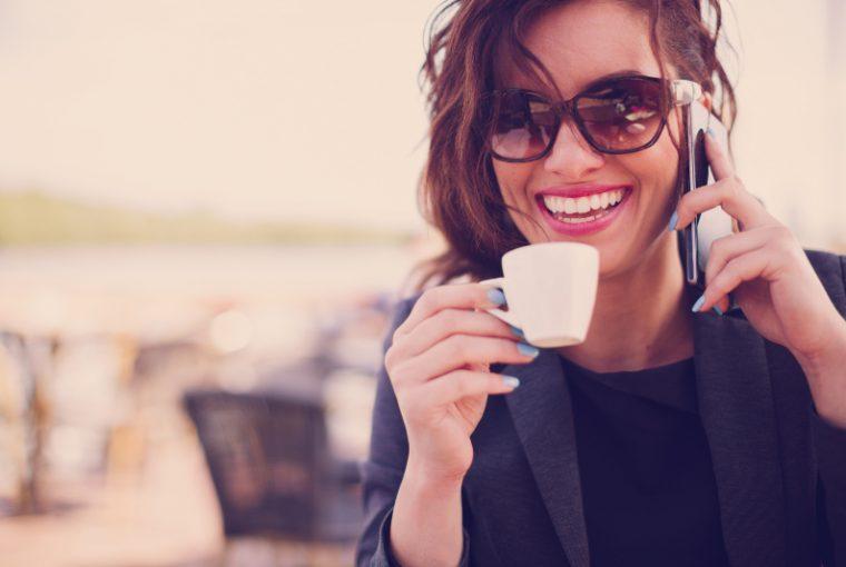 eine Frau telefoniert und trinkt Kaffee