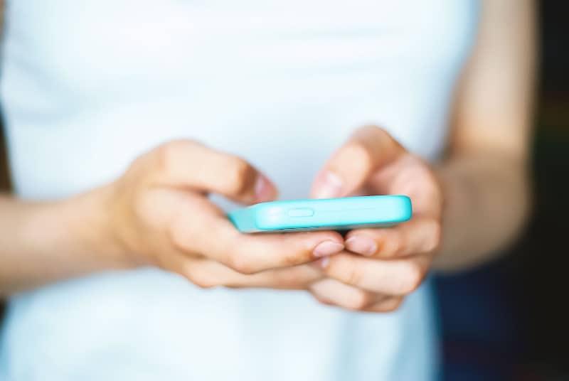 Das Mädchen hält ein Handy in den Händen (2)