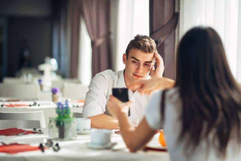 Das Mädchen zeigt dem Mann etwas auf ihrem Handy