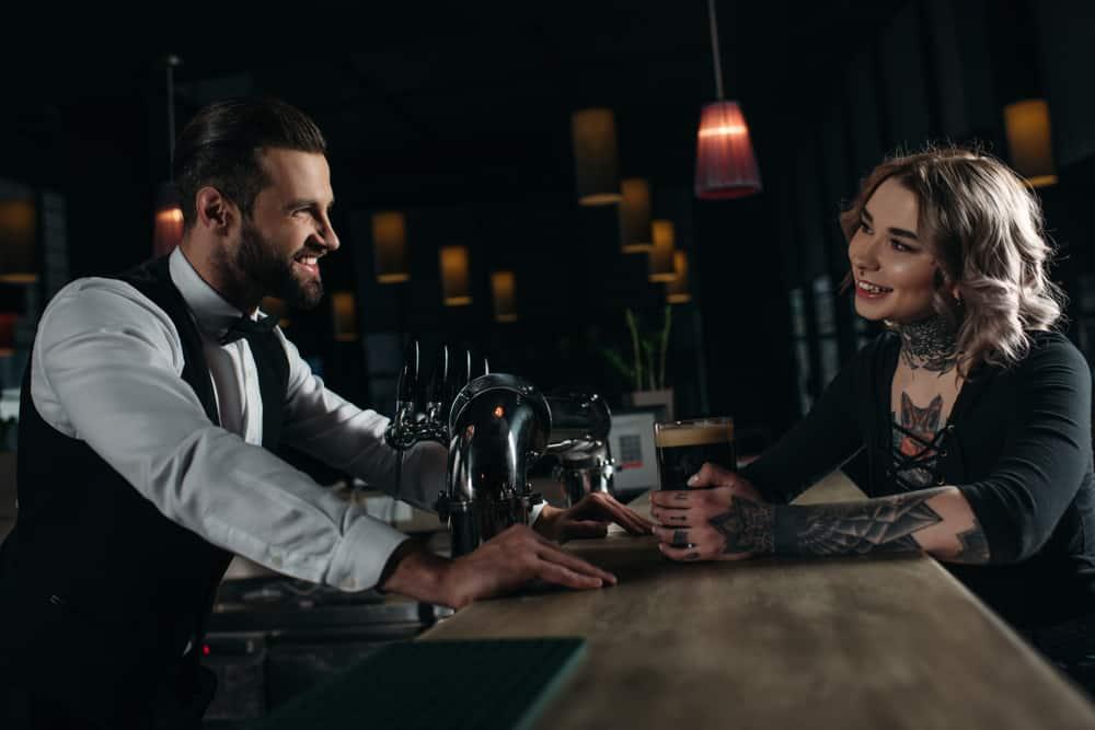 Der Kellner und der Gast der Bar flirten im Cafe