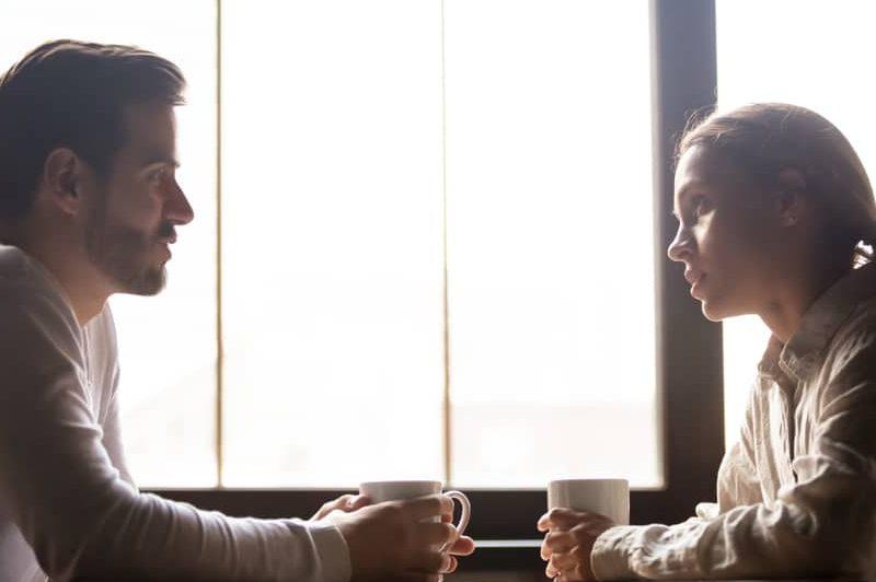 Der Mann und die Frau am Tisch unterhalten sich