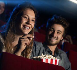 lächelnder Mann und eine Frau, die im Kino sitzen