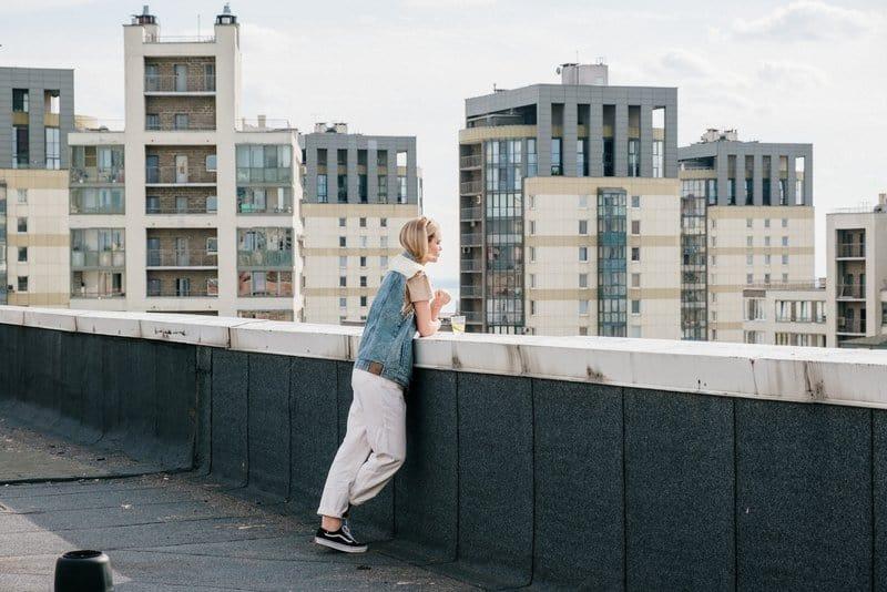 Die Blondine steht auf dem Dach des Gebäudes und beobachtet die Stadt
