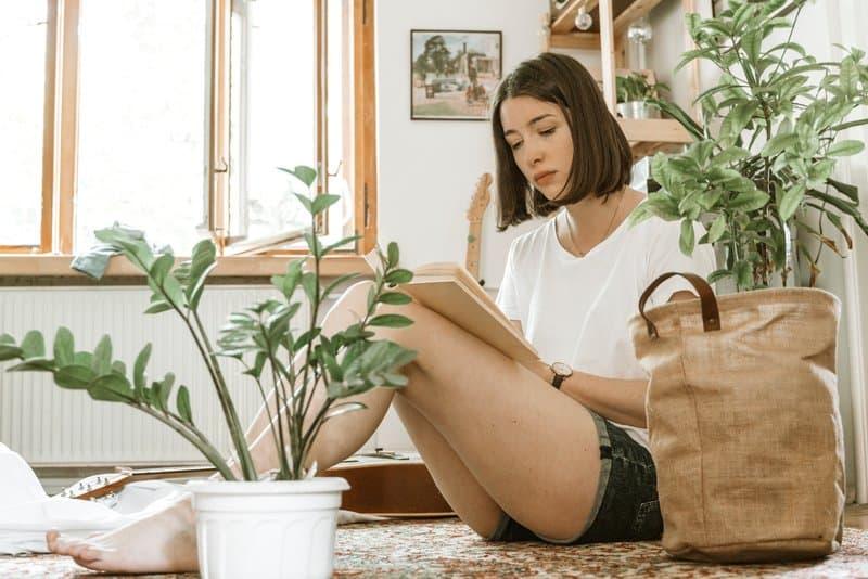 Die Brünette sitzt im Haus auf dem Boden und liest ein Buch
