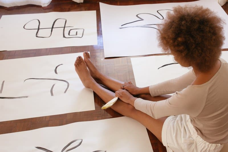 Die Frau sitzt auf dem Boden und zeichnet