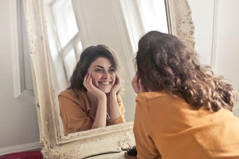 Die Frau steht vor dem Spiegel und lacht
