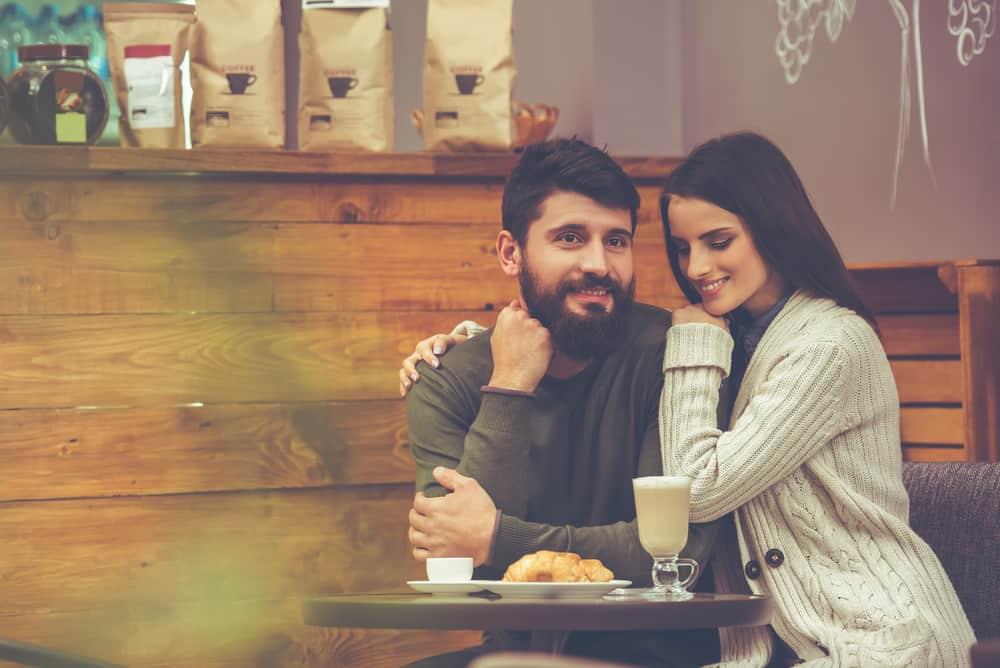 Die Frau umarmte den Mann beim Kaffeetrinken