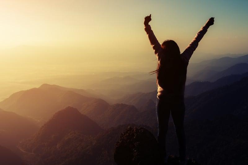 ein Mädchen auf einem Berg mit erhobenen Armen