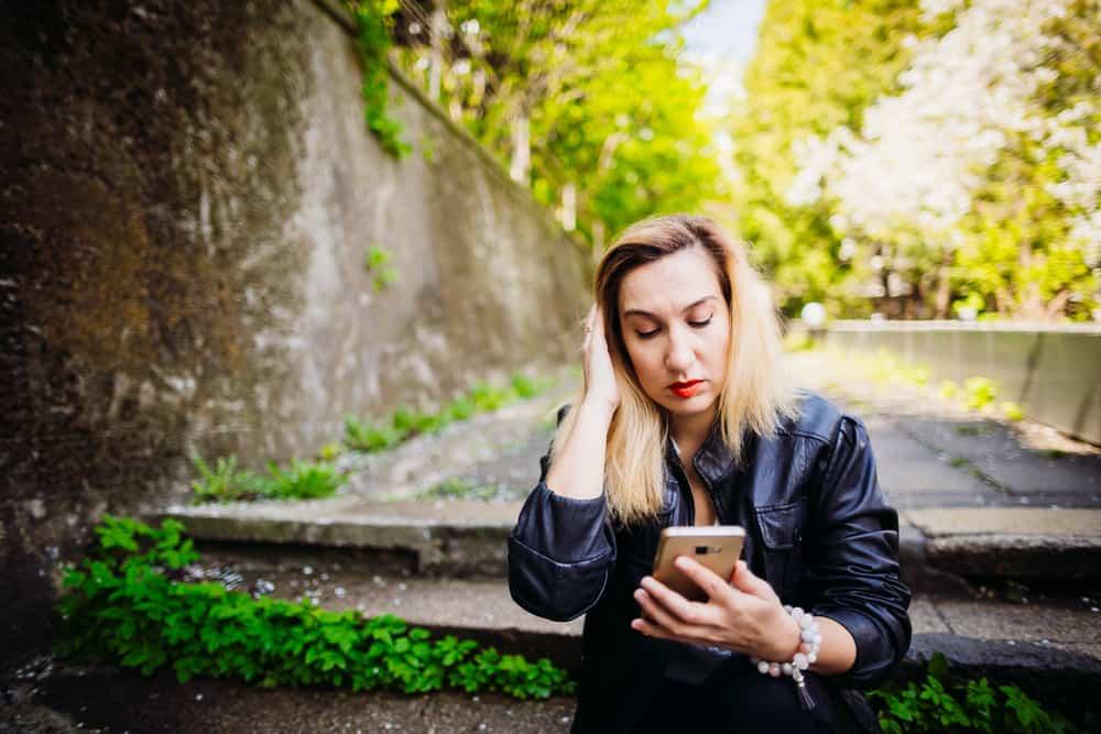 Draußen auf der Treppe sitzt eine Blondine in einer Lederjacke und benutzt ein Handy