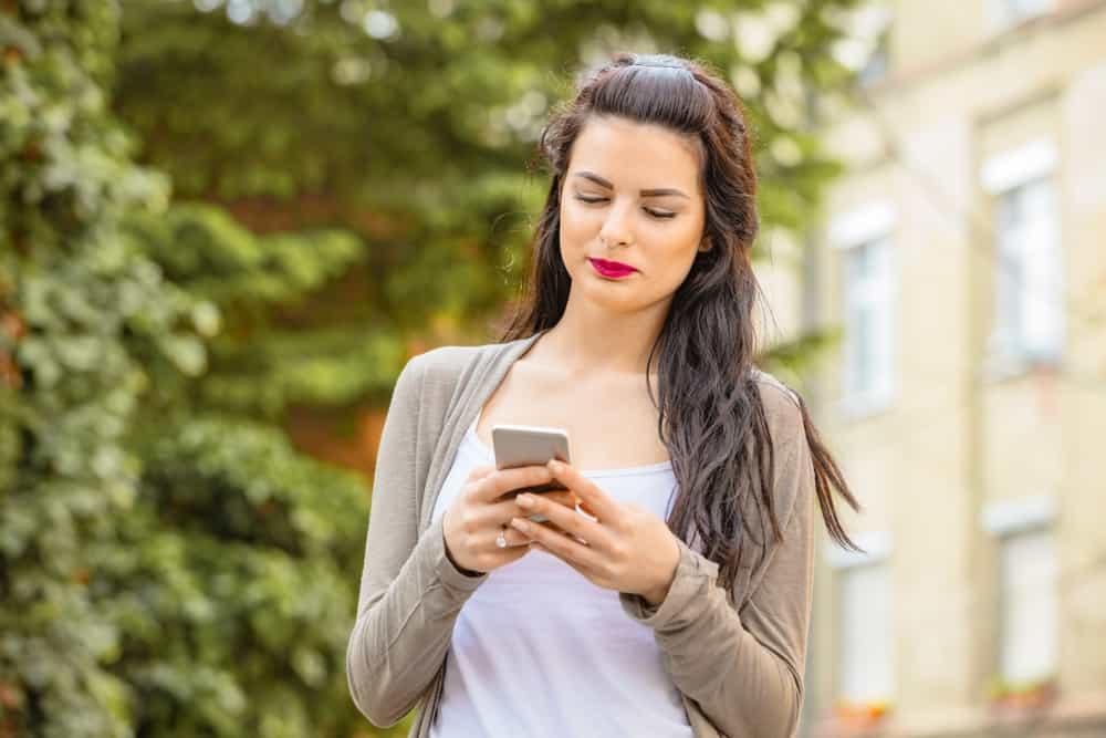 Draußen steht eine schöne Brünette und schreibt eine SMS