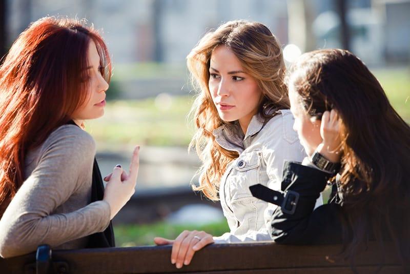 Drei Frauen sitzen auf der Bank und reden