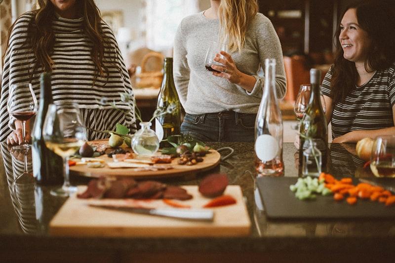 Drei Freundinnen probieren Wein, während sie rumhängen
