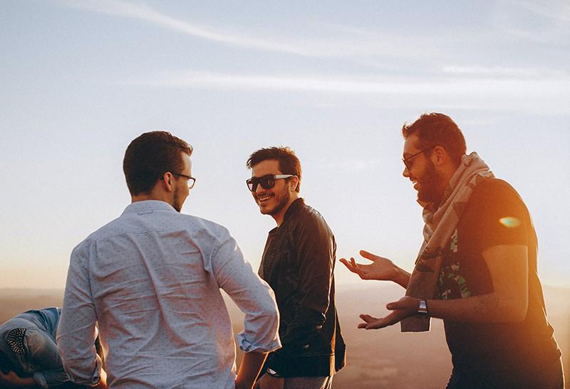 Drei Männer lachen, während sie zusammen stehen und rumhängen