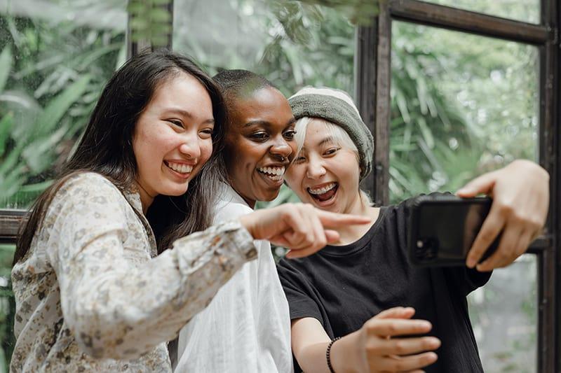 Drei lächelnde Frauen machen ein Selfie, während sie in der Nähe des Fensters stehen