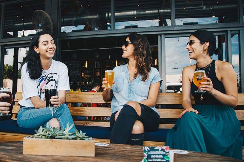Drei lächelnde Frauen sitzen auf der Bank und halten Getränke in der Kneipe