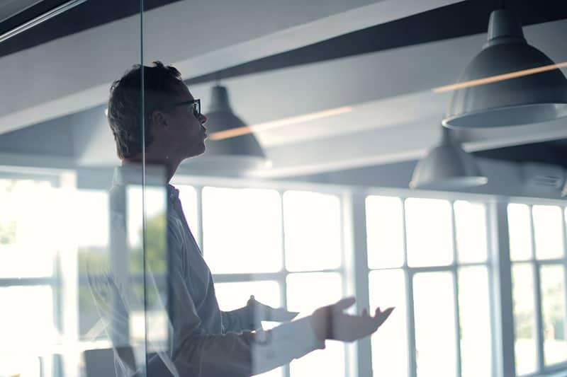 Ein Geschäftsmann redet, während er im Büro steht und mit den Händen gestikuliert