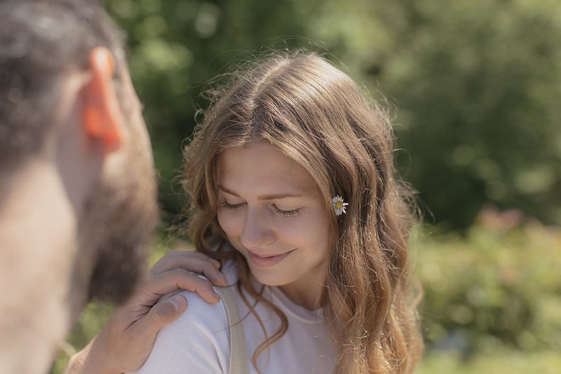 Ein Mann berührte die Schulter seiner Freundin, während sie lächelte