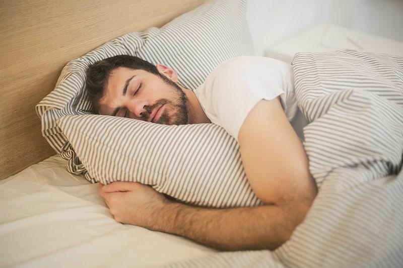 Ein Mann, der fest in einem Bett schläft und ein Bett umarmt