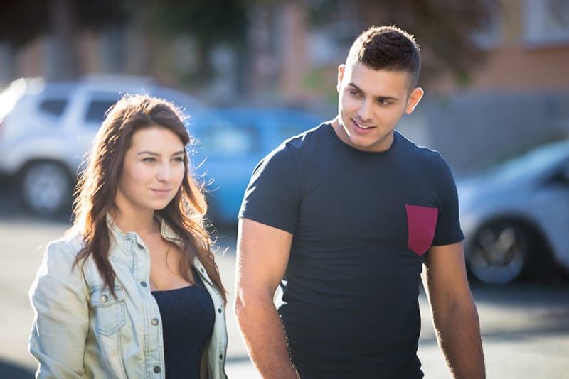 Ein Mann, der mit einer Frau flirtet, während er zusammen auf dem Bürgersteig geht