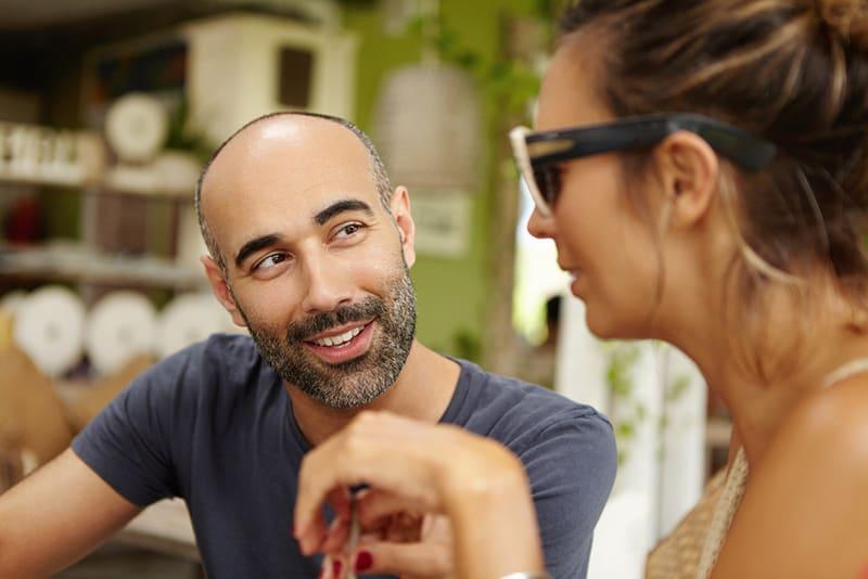 Ein Mann, der mit einer Frau flirtet, die eine Sonnenbrille trägt, während er in der Cafeteria sitzt