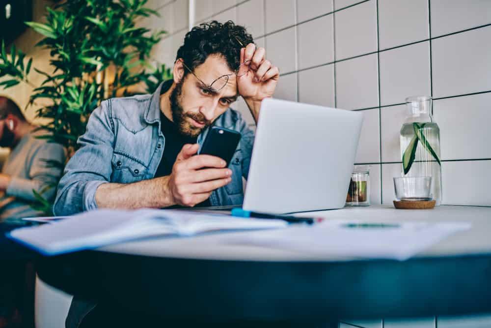 Ein Mann sitzt an seinem Schreibtisch und liest ungläubig eine SMS