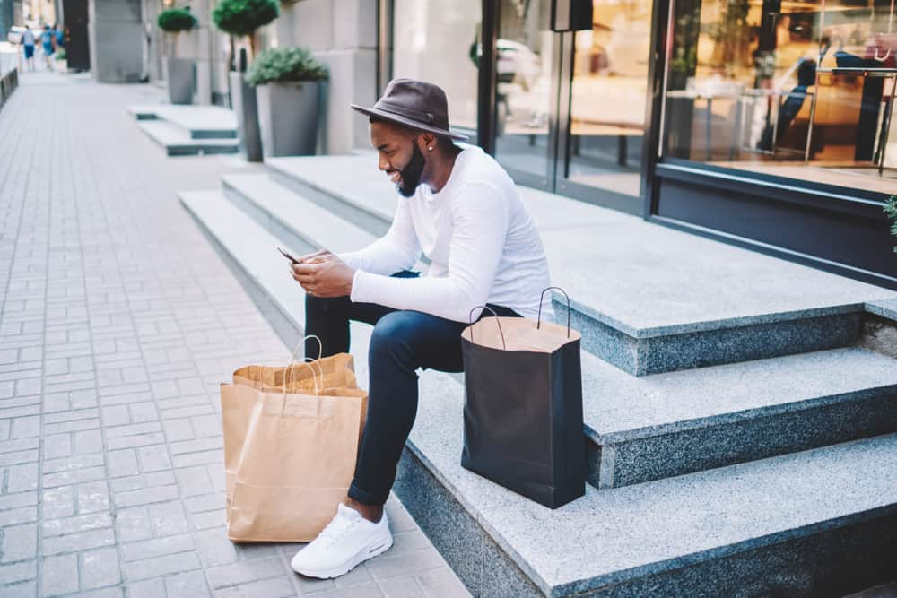 Ein Mann sitzt auf der Treppe und einen Knopf am Telefon