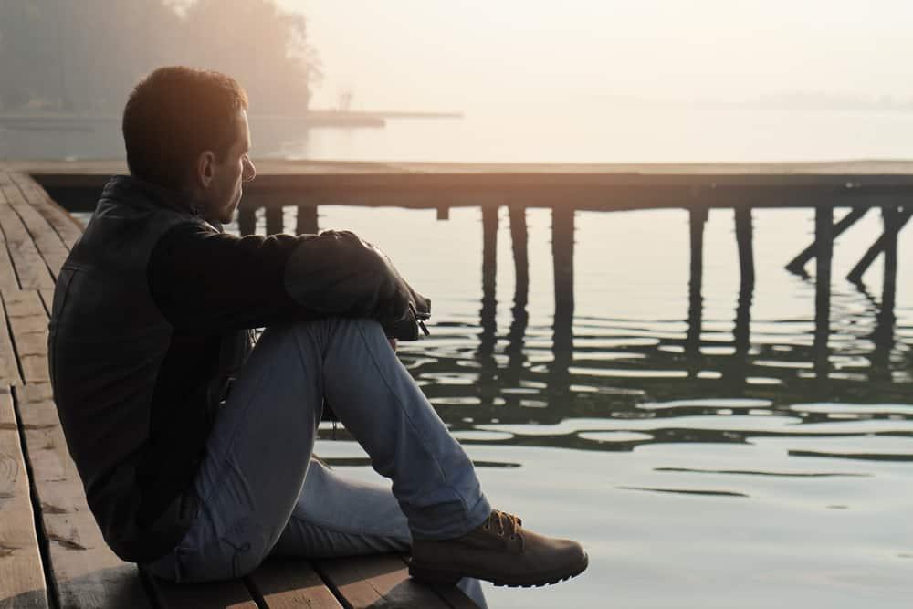 Ein Mann sitzt auf einem alten Holzsteg und beobachtet den Sonnenuntergang