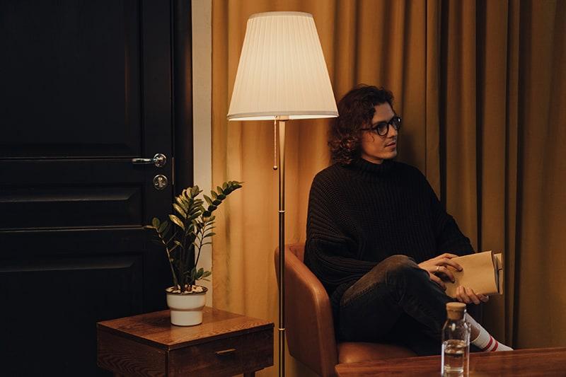 Ein Mann sitzt im Sessel und hält ein Buch