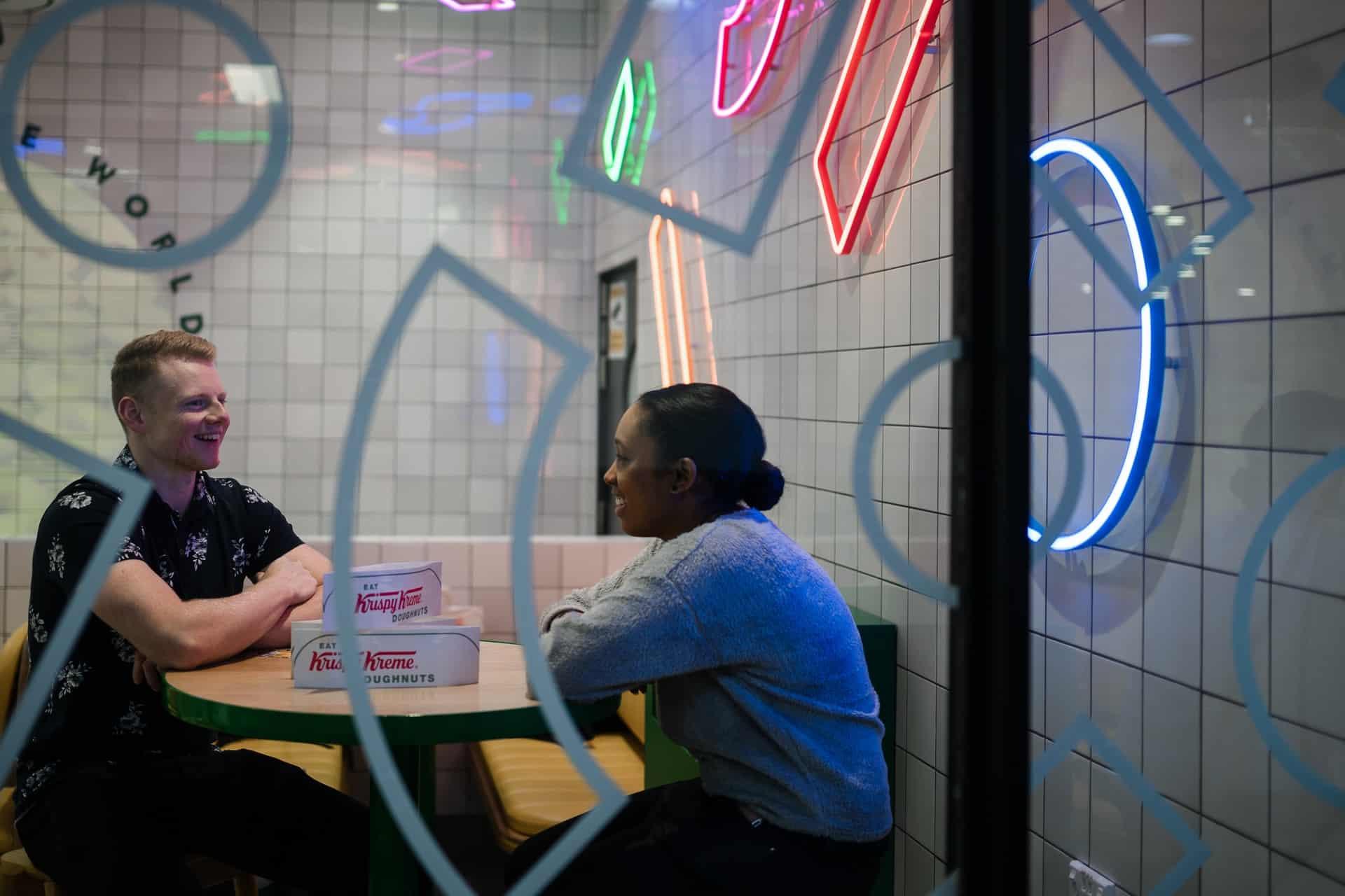 Ein Mann sitzt mit einer Frau an einem Tisch und redet