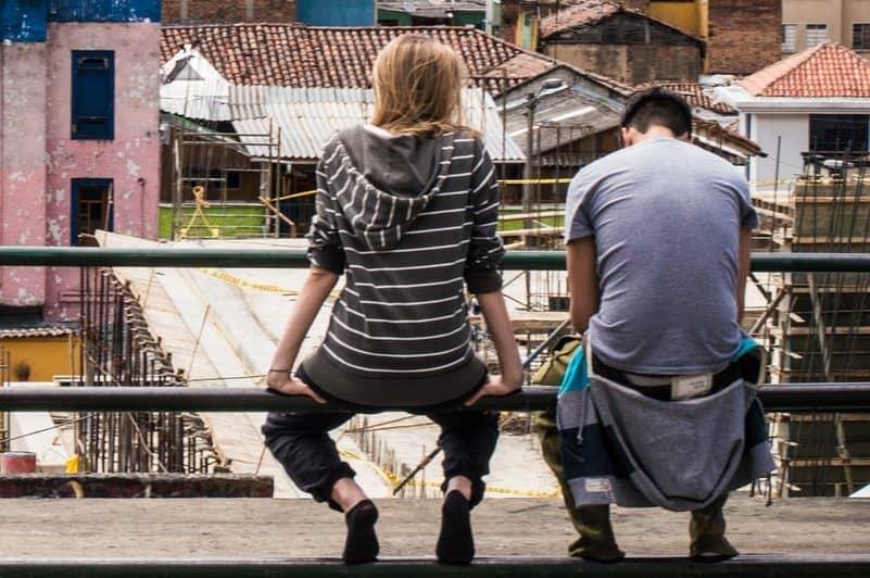 Ein Mann sitzt mit einer Frau auf einem Zaun und redet