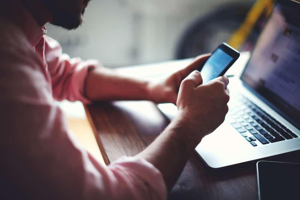 Ein Mann sitzt und benutzt ein Handy