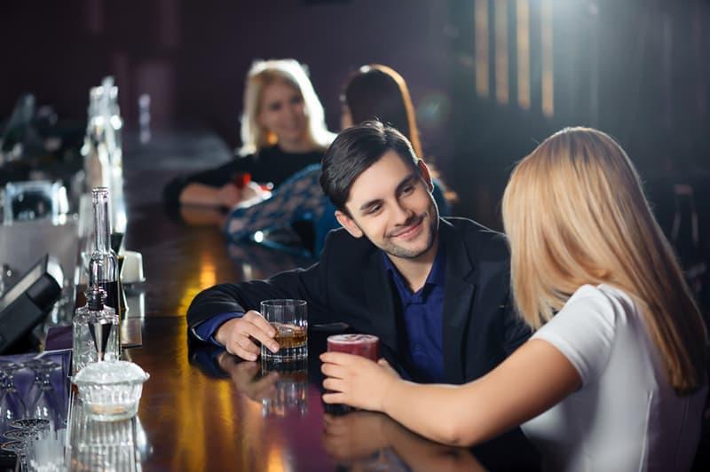 Ein Mann spricht mit einer Frau, während er an der Theke im Club sitzt
