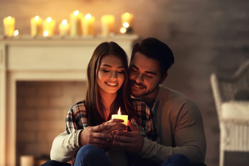 Ein Mann umarmt eine Frau von hinten, während er eine Kerze zusammenhält
