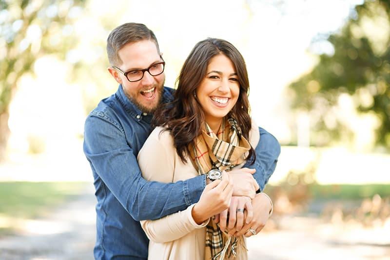 Ein Mann umarmt seine lachende Frau von hinten, während er im Park steht