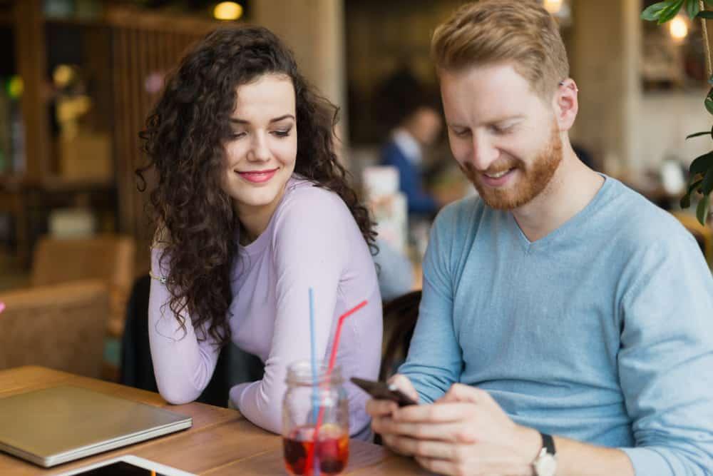 Ein Mann und eine Frau sitzen an einem Tisch, den er am Telefon tippt