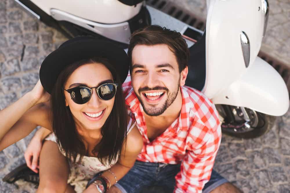 Ein Mann und eine Frau sitzen neben dem Motor und umarmen sich lachend