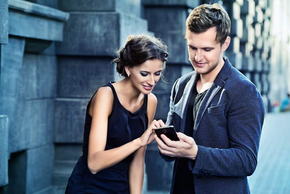 Ein Mann und eine Frau stehen auf, als sie sein Telefon berührt
