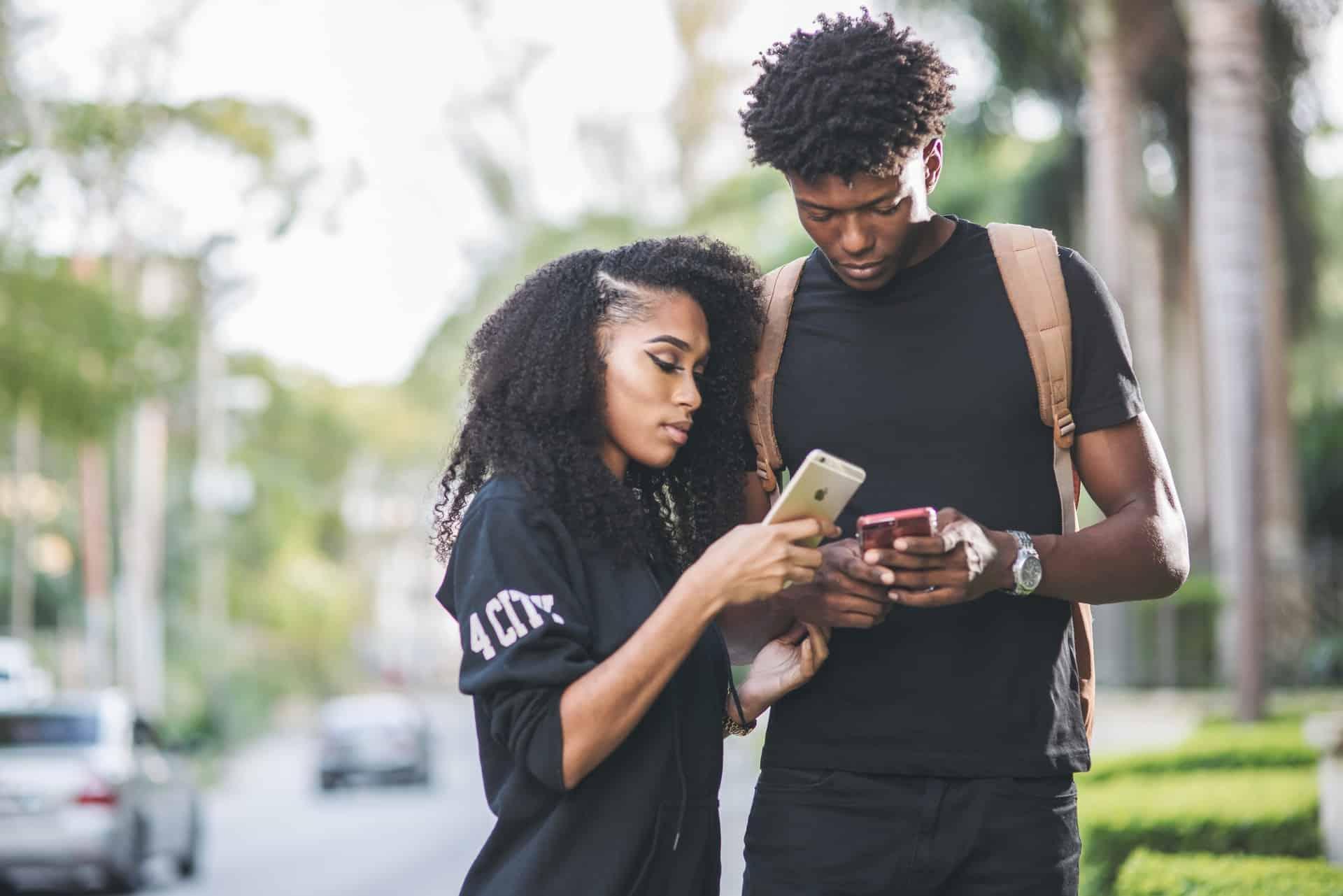 Ein Mann und eine Frau stehen mit einem Telefon in der Hand
