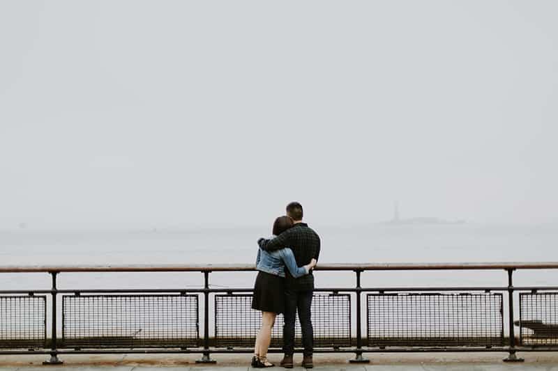 Ein Paar umarmt sich, während es vor einem Zaun in der Nähe des Gewässers steht
